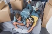 magas, szög, kilátás a boldog fiatal pár fénykép album ágyon miközben beköltöző új otthonában