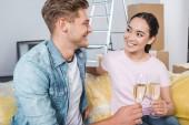 Interracial junges paar klirrende Gläser Champagner nach dem Umzug in neues Zuhause