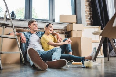 beautiful young couple sitting on floor at new home surrounded with boxes