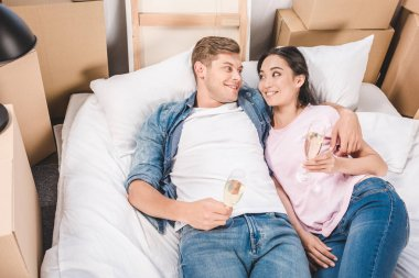 high angle view of young couple lying in bed with champagne glasses after moving into new home