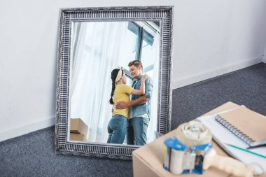 mirror reflection of beautiful couple embracing after moving into new home