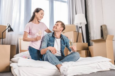 beautiful young couple sitting on bed with champagne while moving into new home