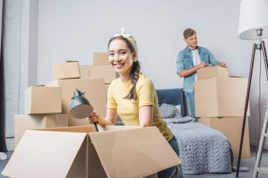 happy young couple unpacking boxes while moving into new home