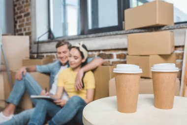 beautiful young couple sitting on floor while moving into new home with coffee to go on foreground