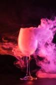 Fotografia bicchiere pieno di fumo dentellare su priorità bassa nera