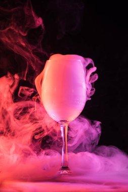 wine glass full of pink smoke on dark background