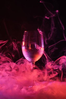 empty glass with pink smoky swirls around on black background