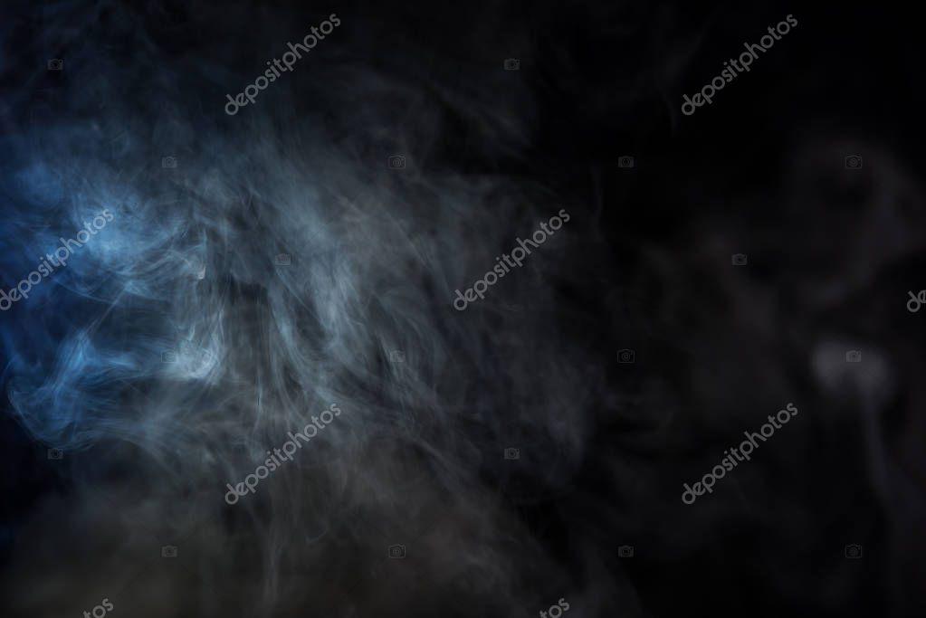 grey tobacco smoke with blue light on black background