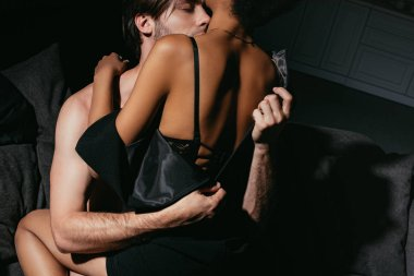young multiracial sexy couple in black clothing on sofa