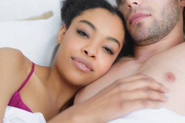 partial view of multiethnic young couple in love lying in bed together in morning