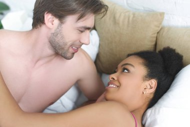 portrait of smiling multiethnic young couple in love lying in bed together in morning