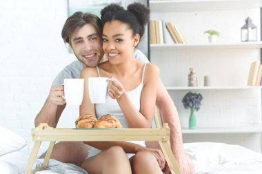 portrait of multiracial young couple with cups of coffee having breakfast in bed in morning at home