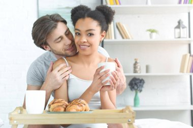 portrait of multiracial young couple having breakfast in bed in morning at home