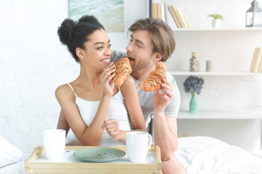 Portrait of multiracial young couple having breakfast in bed in morning at home stock vector