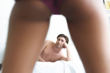 selective focus of man looking at girlfriend in underwear while lying on bed at home