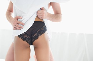 partial view of man hugging girlfriend in underwear at home