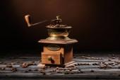 Retro kafe mlýnek na rustikální dřevěný stůl rozlila se kávová zrna