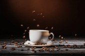 close-up shot of cup with coffee beans falling around on rustic wooden table