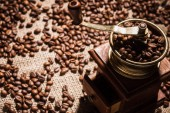 Photo close-up shot of coffee grinder on sackcloth spilled with coffee beans