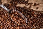 Close-up shot z scoop a pražená kávová zrna vylila na pytloviny