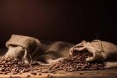 pytle se kávová zrna na rustikální dřevěný stůl na tmavě hnědé pozadí