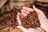 oříznutý snímek ženy držící pražená kávová zrna