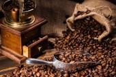 Detailní záběr mlýnek na kávu vintage s kopečkem a žíně na rustikální dřevěný stůl