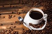vysoký úhel pohled šálek kávy na rustikální dřevěný stůl vylila s fazolemi
