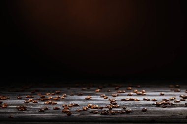 rustic wooden table spilled with coffee beans on black