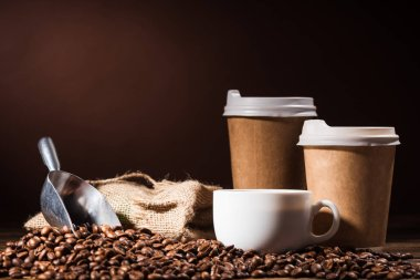 close-up shot heap of coffee beans with paper cups, scoop and mug on rustic wooden table