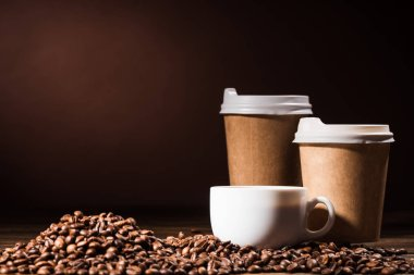 close-up shot heap of coffee beans with paper cups and mug on rustic wooden table