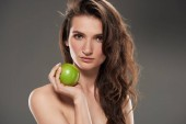 attractive young woman with fresh green apple, isolated on grey