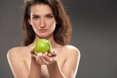 Fotografie naked girl with fresh green apple, isolated on grey