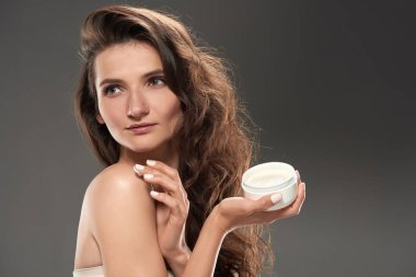 young tender woman applying moisturizing face cream, isolated on grey