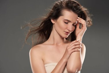 brunette tender woman with closed eyes in bra, isolated on grey