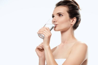 attractive girl in towel drinking water from glass, isolated on white