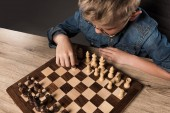 Fotografie elevated view of little boy in eyeglasses playing chess at table