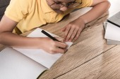 Fotografie partial view of schoolboy in eyeglasses writing in empty textbook at table with stack of books