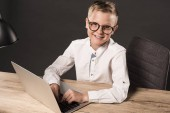 Fotografie happy little boy in eyeglasses looking at camera while sitting at table with laptop and lamp on grey background