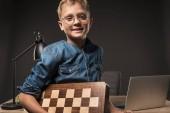Fotografie šťastný chlapec v brýlích při pohledu na fotoaparát a držení šachovnici u stolu s notebookem a lampa na šedém pozadí