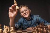 smiling little boy in eyeglasses holding chess figure over chessboard isolated on grey background