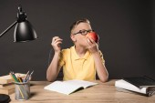 Fotografie schoolboy in eyeglass eating apple and doing homework at table with lamp, books, colour pencils and textbook on grey background