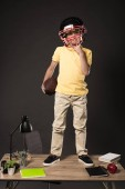Fotografie schoolboy in american football helmet holding ball and standing on table with books, plant, lamp, colour pencils, apple, clock and textbook on grey background