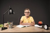 Fotografie smiling schoolboy in eyeglasses with folded arms sitting at table with books, plant, lamp, colour pencils, apple, clock and textbook on grey background