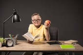 Fotografie smiling schoolboy in eyeglasses holding apple and reading book at table with books, plant, lamp, colour pencils, clock and textbook on grey background