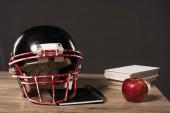 Fotografia Chiuda sulla vista del casco di football americano, libro di testo, apple e pila di libri su sfondo grigio