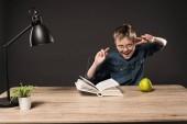 izgatott a kisfiú a szemüvegek csinál béke jelek asztalhoz a könyv, a körte, a növény és a lámpa szürke háttér
