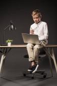 vážné chlapeček drží brýle a pomocí přenosného počítače, zatímco sedí na stole s rostlin a lampu na šedém pozadí