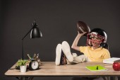 Fotografie smiling schoolboy in american football helmet holding ball and sitting with legs on table with books, plant, lamp, colour pencils, apple, clock and textbook on grey background