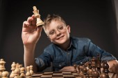 selective focus of little boy in eyeglasses holding chess figure over chess board on grey background